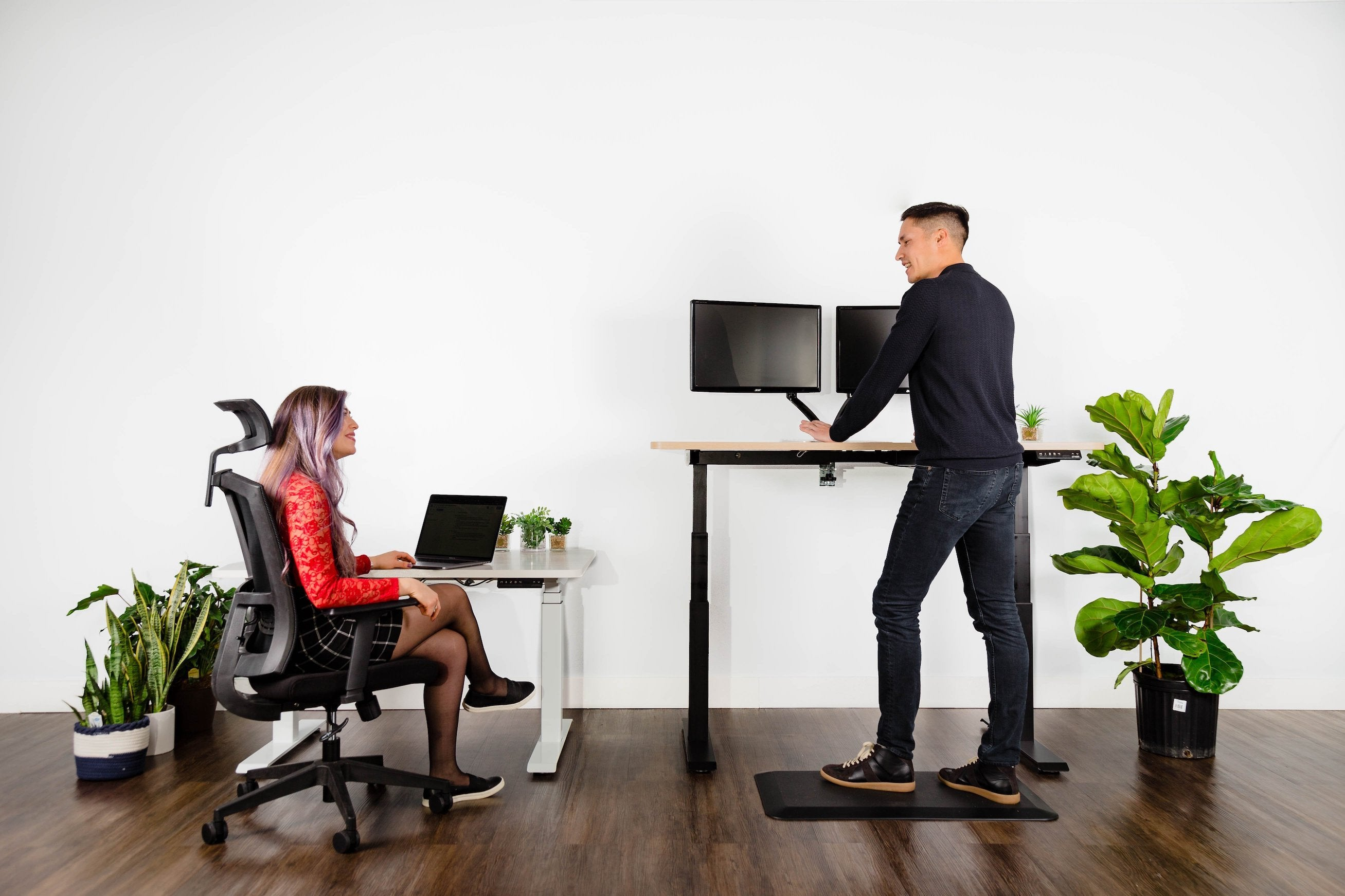 Effydesk in use at an office, one sitting and working employee, one standing and working employee