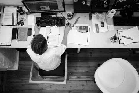 Large cluttered desk is too big for worker to reach their stuffs