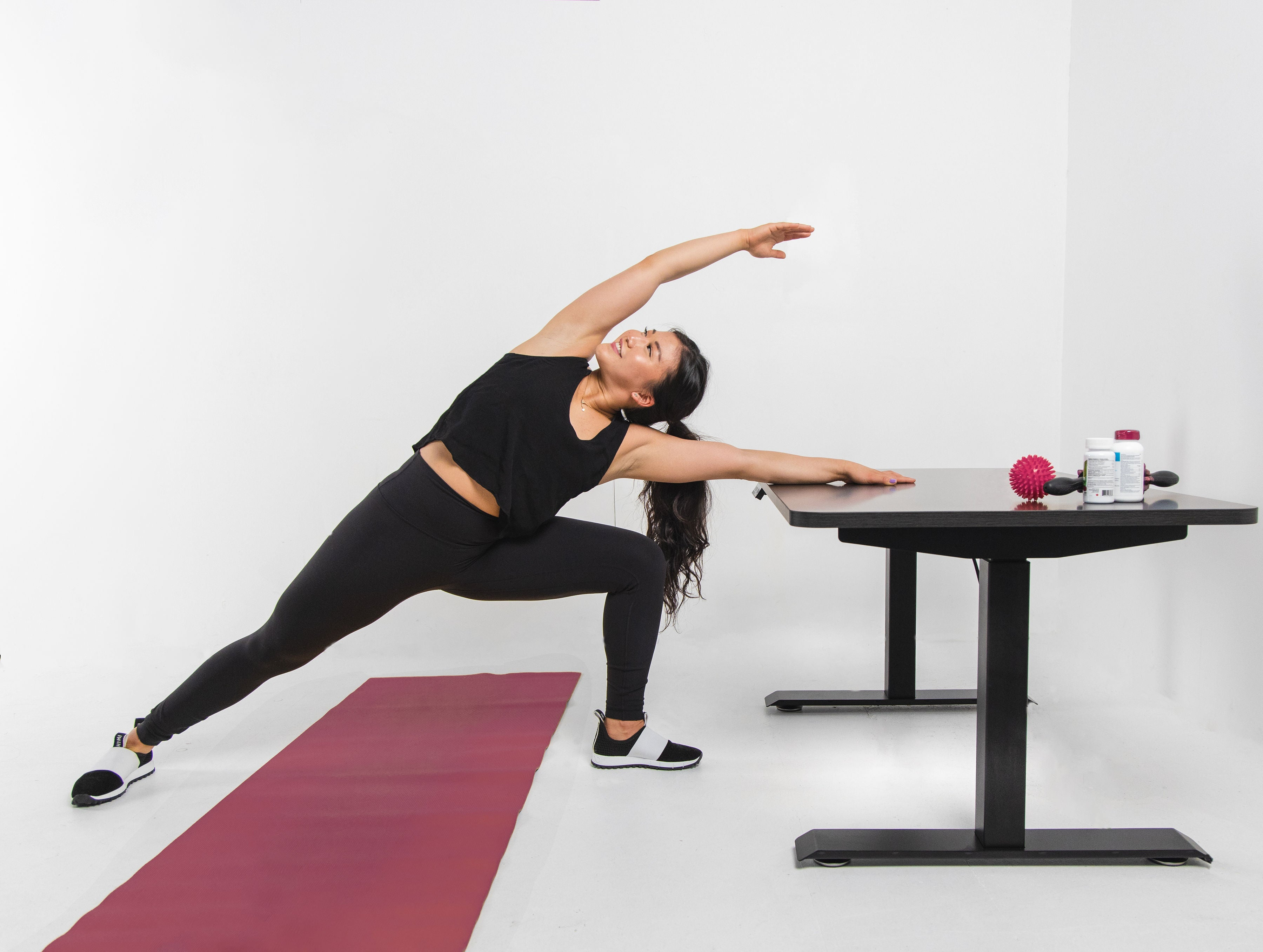 woman stretching at effydesk height adjustable automatic standing desk to reduce back pain