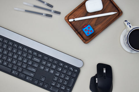 desk flat lay from above, try with pens and airpods, coffee, keyboard and camera
