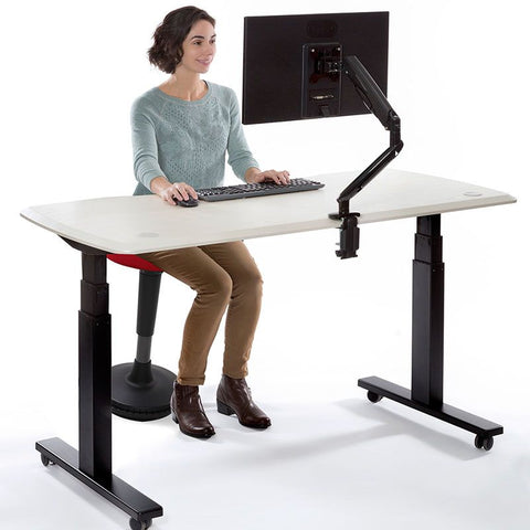 sitting on wobble stool with standing desk