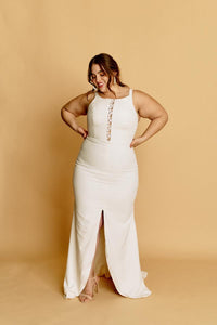 A plus size fitted mermaid wedding dress in rich smooth crepe, with a high neck, lace keyhole, and centre slit