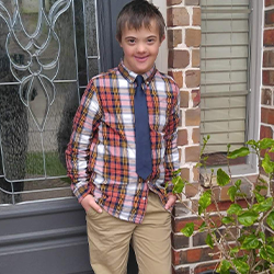 Image of Ry standing infront of a house, wearing a                 checkered shirt and navy blue tie