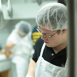 Image of Nolan Stillwell, a young man with Down syndrome in                 a commercial kitchen wearing a white apron, navy shirt and a                 hairnet.