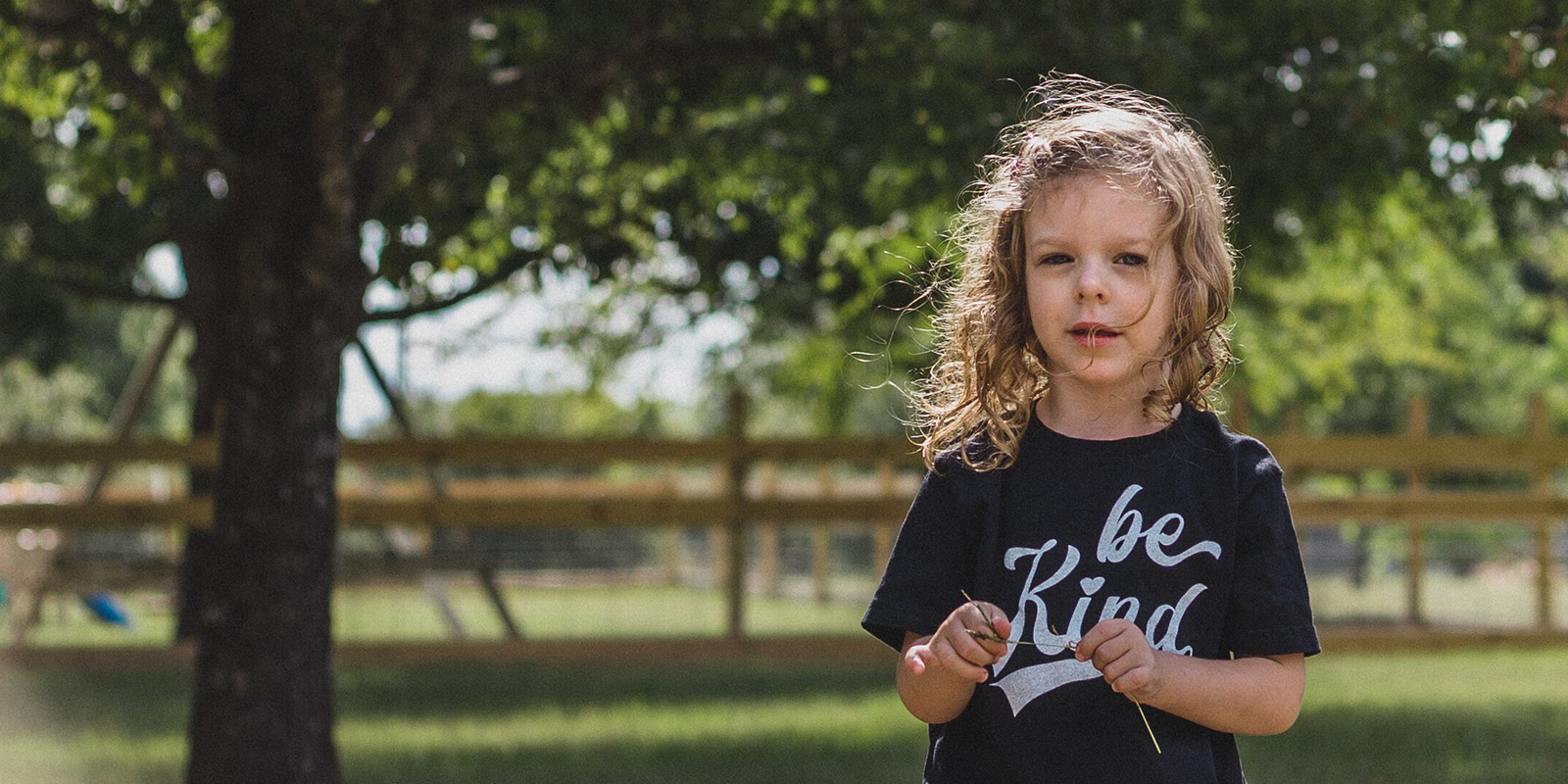 "Young girl wearing shirt that says ""Be Kind"""