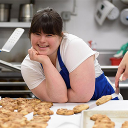 Image of Collettey, a woman with Down syndrome, in a                 commercial kitchen wearing a blue apron smiling with some                 cookies.