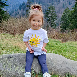 """Image of toddler, Ivy, wearing a white shirt with the                 design""""Spark Joy"""""""
