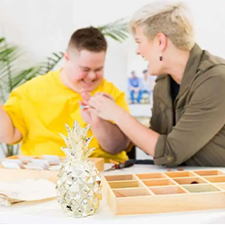 Image of Margrit Co. founder, Maggie with her brother who                 was born with Down syndrome. They are sitting at a desk making                 jewellry.