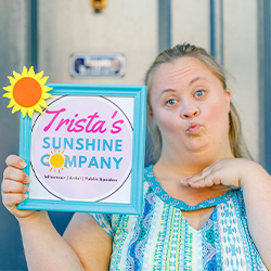 Image of Trista holding up a blue frame that say's Trista's                 Sunshine company