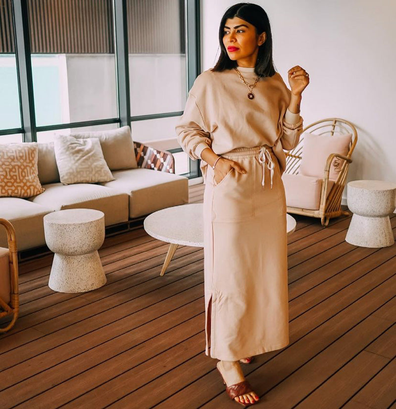 Neha wears the Game Oversized Sweat in Camel with the Game Skirt.