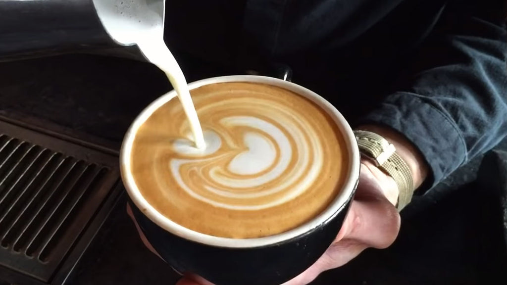 Milk pouring from a stainless steel frothing pitcher into a latte to make latte art into a cappuccino cup.