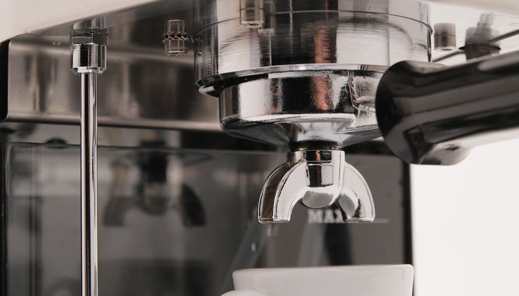 Up close shot of a shiny and reflective Gaggia Classic, with a double spouted portafilter locked into the machine.