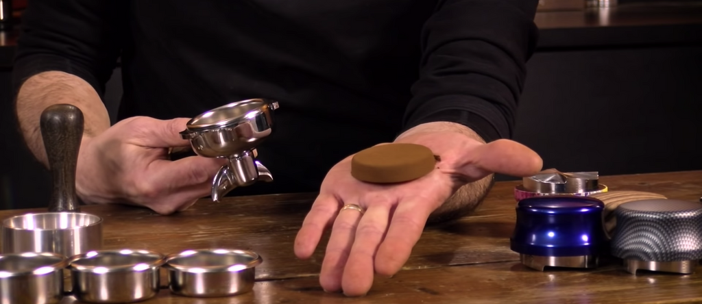A dry puck of coffee in an open palm, with an empty portafilter in the other hand. There is a wooden table underneath the hand with three Asso Jacks one one side, and empty filter baskets and other accessories on the other side.