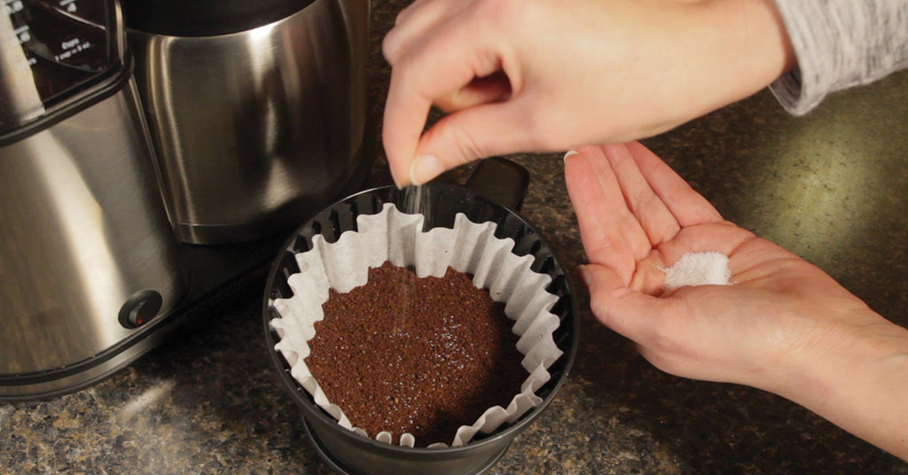 Adding a pinch of salt to a filter of ground coffee
