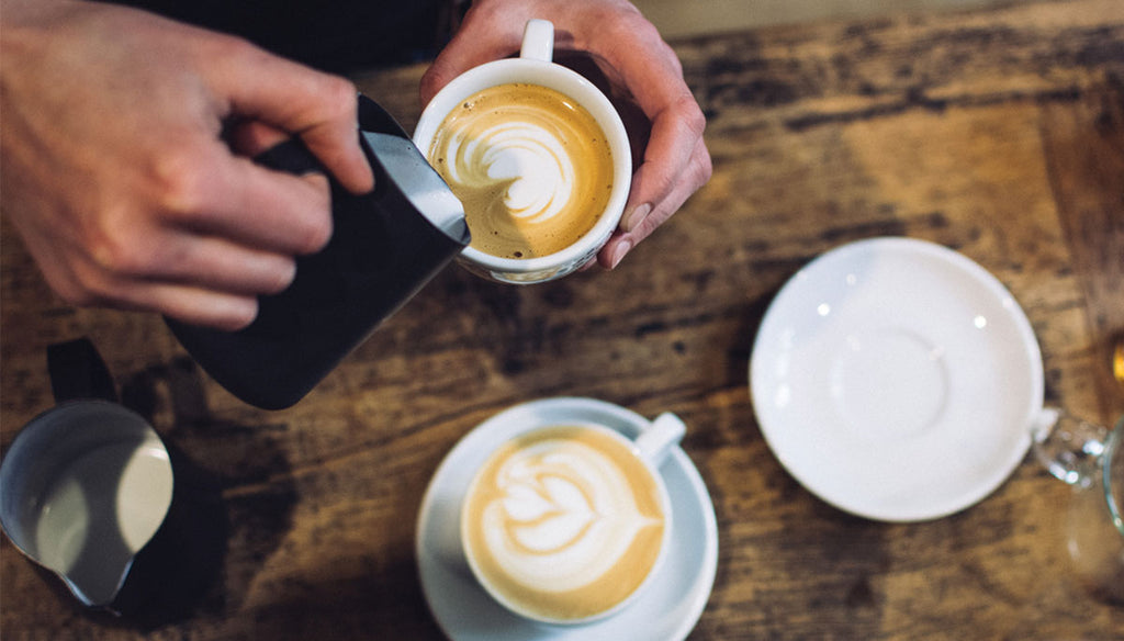 Milk pouring from a black carafe into a white cappuccino mug to form latte art. Saucers, a different latte art-filled cup, and other assortments are on a rustic wooden table.