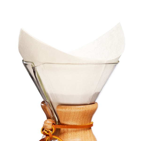 A Chemex pre-folded filter square resting in a Chemex coffee maker