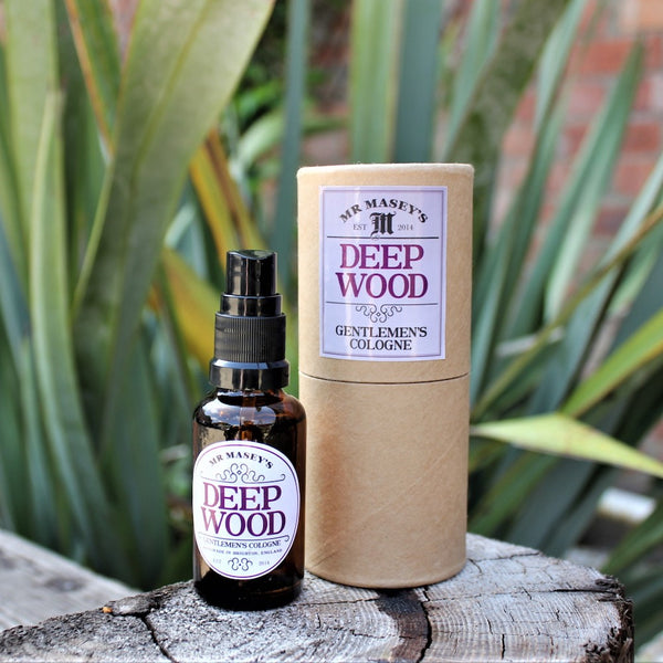 Mr Masey's Deep Wood Handmade Vegan Cologne bottle and box on a tree stump