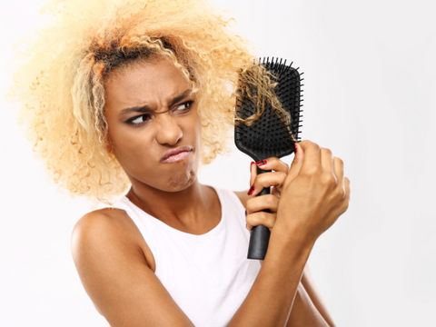 Black woman struggling to comb hair