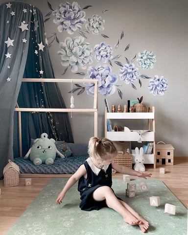 Colorful nursery with flower wallpaper and green Play Mat, where a kid is playing with wooden toys