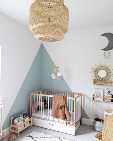 Blue colorful nursery with white crib and light wood details
