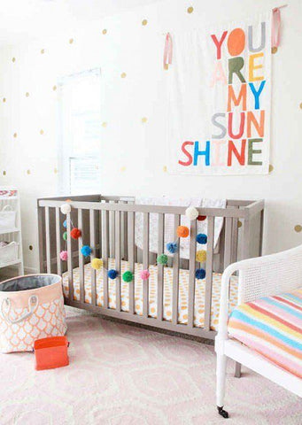 """Colorful nursery with a rainbow tapestry in the wall """"You are my sunshine"""""""