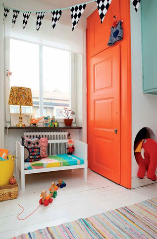 Colorful nursery with a door painted in bright orange