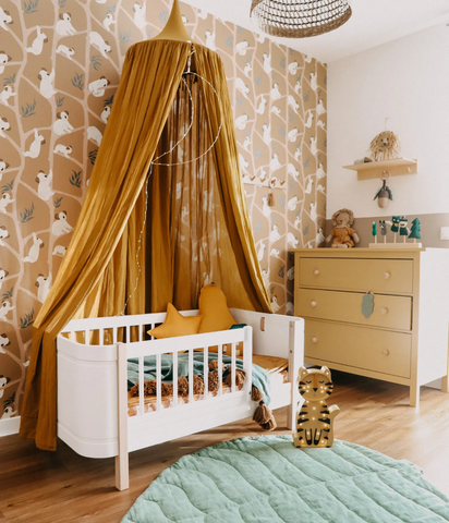 Colorful nursery in tones of yellow, with a white crib, mustard canopy and patterned wallpaper on the back