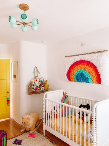 Colorful nursery with rainbow tapestry and yellow door