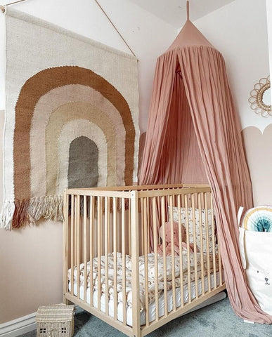 Colorful nursery with tones of pink, a rainbow tapestry and a pink canopy