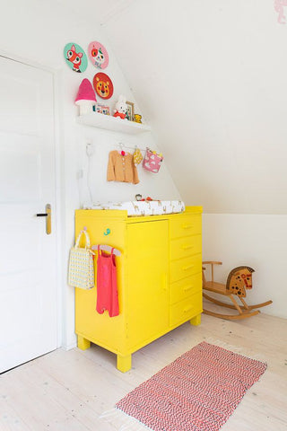 Colorful yellow dresser in the corner of a nursery