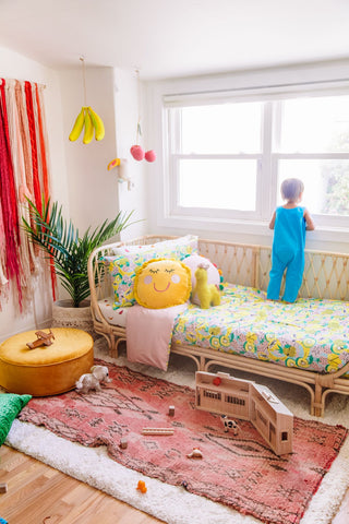 Colorful nursery with a patterned bedding in fruit salad and a big pink rug
