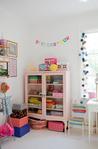 Nursery with colorful cabinet painted in pink