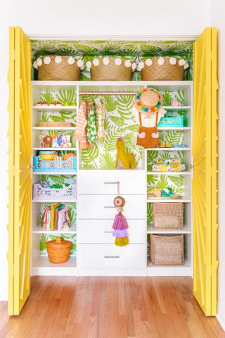 Colorful nursery wardrobe, with a flower wallpaper, yellow doors and baskets organizing the clothes