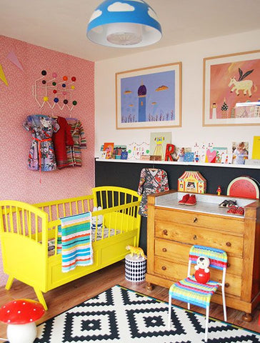 Colorful nursery, with a yellow crib and a patterned wallpaper
