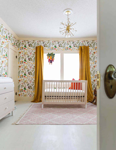 Colorful nursery with plant wallpaper, yellow curtains, pink rug and golden ceiling lamp
