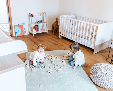Girls playing with wooden toys on Green Playmat
