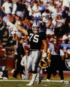 Howie Long Autographed Oakland Raiders 16x20 Holding Ball Up- Beckett Auth *Black