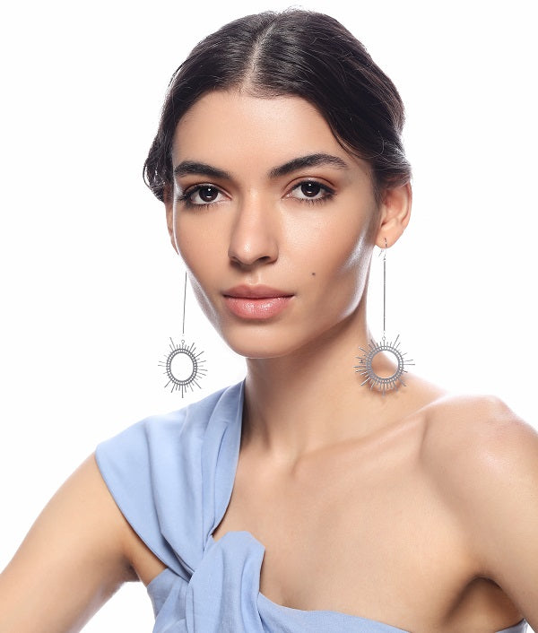 Silver Sun Dangler Earrings by FASHKA, worn by the model.