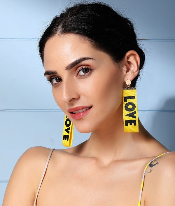 Yellow Love Dangler Earrings by FASHKA, side pose by a model.