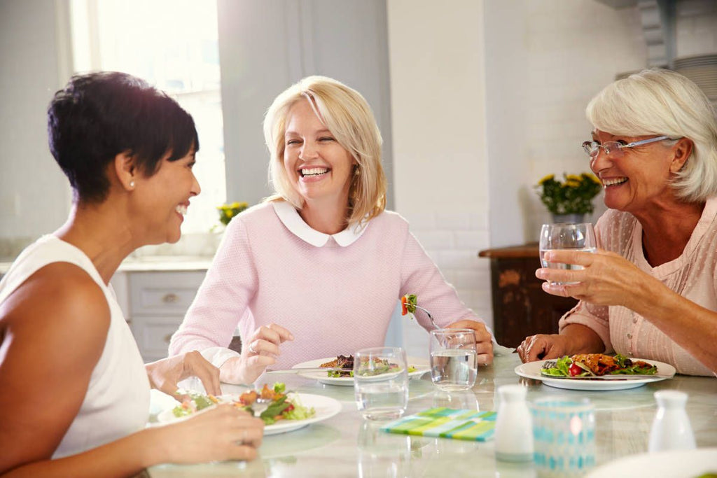 Mature Female Friends Enjoying Meal At Home   Bloated Fat Cells: Overflowing With Inflammation?   fat cell function