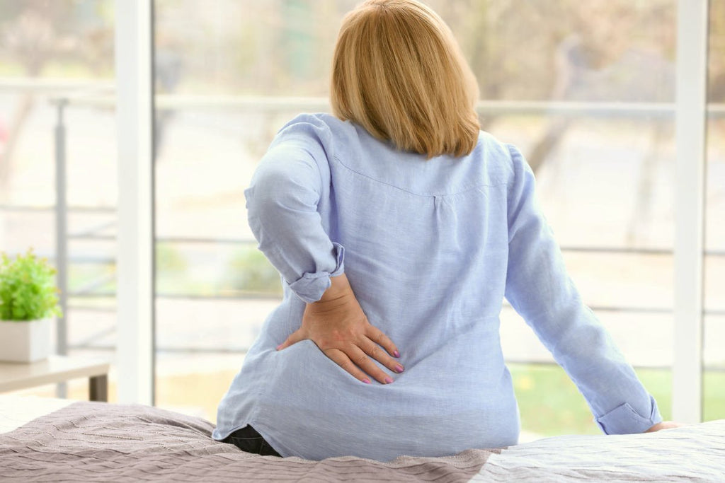 Senior woman suffering from backache at home | Calcium To Magnesium: How The Ratio Affects Your Health | do calcium and magnesium compete for absorption