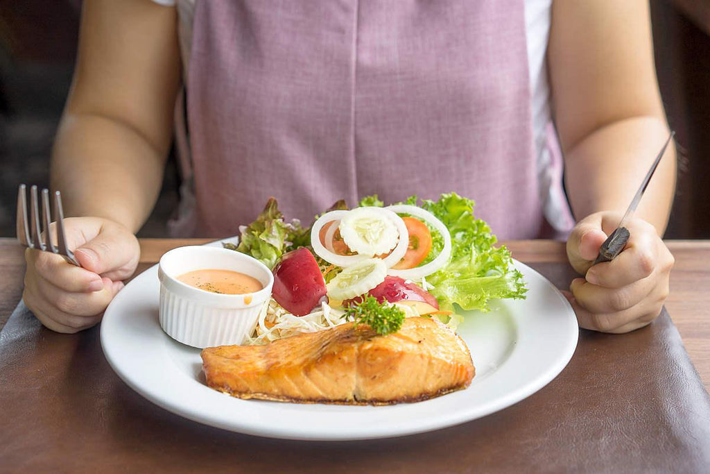 Women eating salmon steak on white plate   Bloated Fat Cells: Overflowing With Inflammation?   what are fat cells