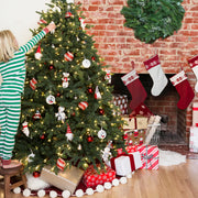 child decorating christmas tree next to fireplace hung with stockings