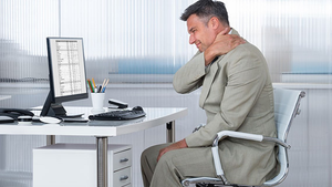 Man holding kneck while sitting at a work desk