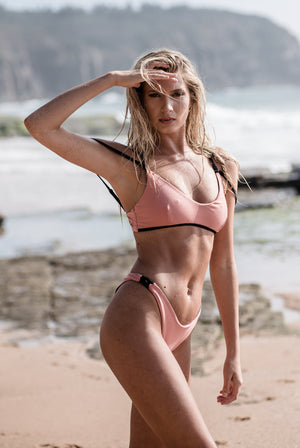 Woman wearing sustainable swimwear top and eco-friendly swimwear bottoms in pink with black detail. Sustainable Swimwear Fashion that is adjustable, reversible and convertible. This is the front view.
