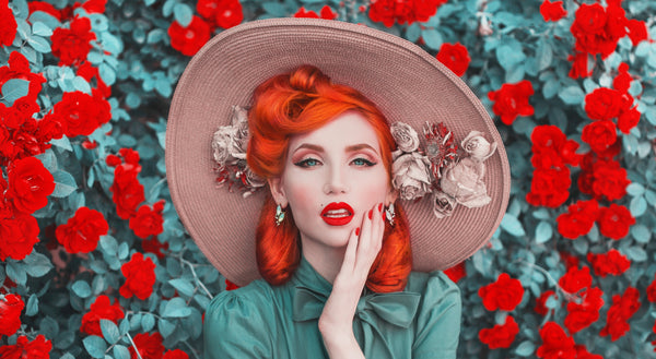 Beautiful women with red-orange hair, red lipstick, and wearing a sunhat.