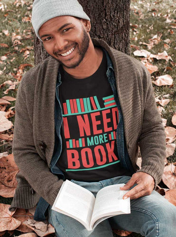 Man reading book wearing I Need More Books T-Shirt