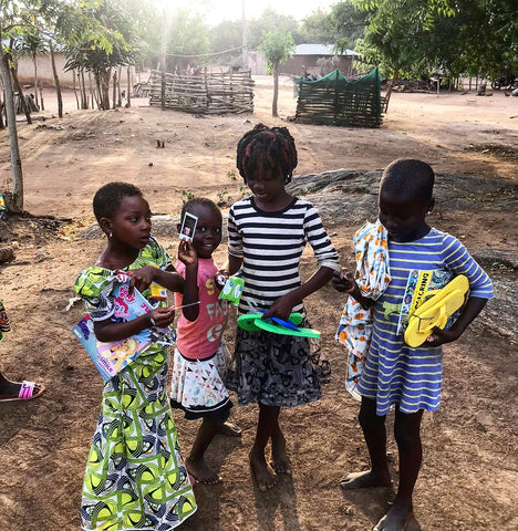 moon and lola children in togo africa with flipflops and polaroid pictures