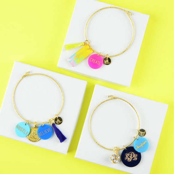 Moon and Lola - Nora Bangle Bundle with a variety of charms on a yellow background
