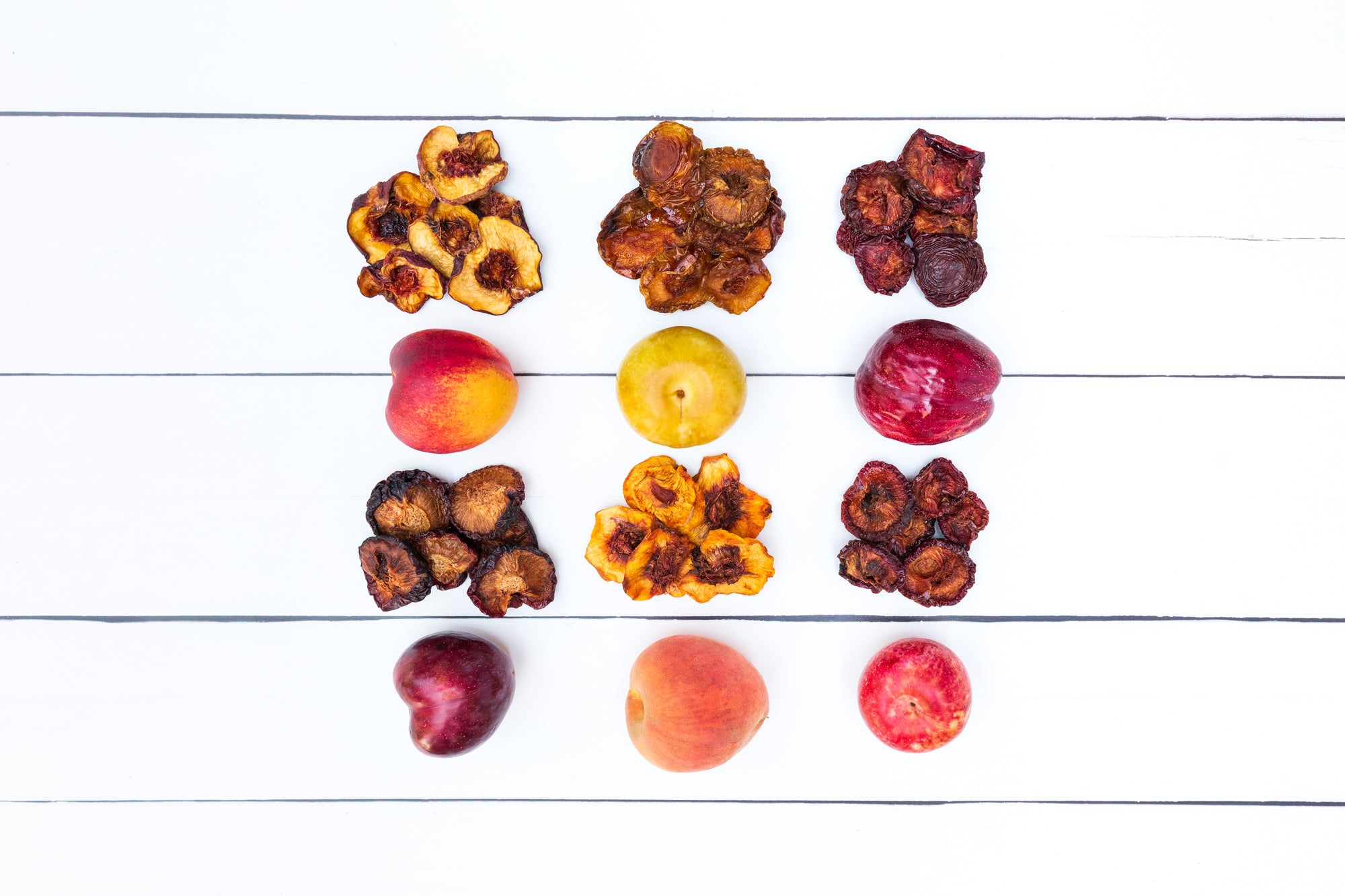 Multiple dried fruit varieties next to their fresh counterparts
